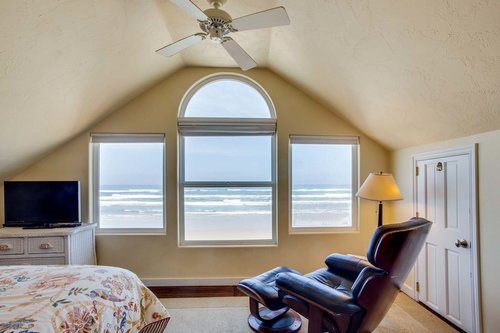 Relax in the master bedroom with ocean views and  comfy chair.