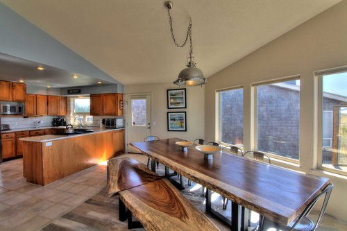 Both the stunning dining area and the amazing kitchen share the stunning vistas.