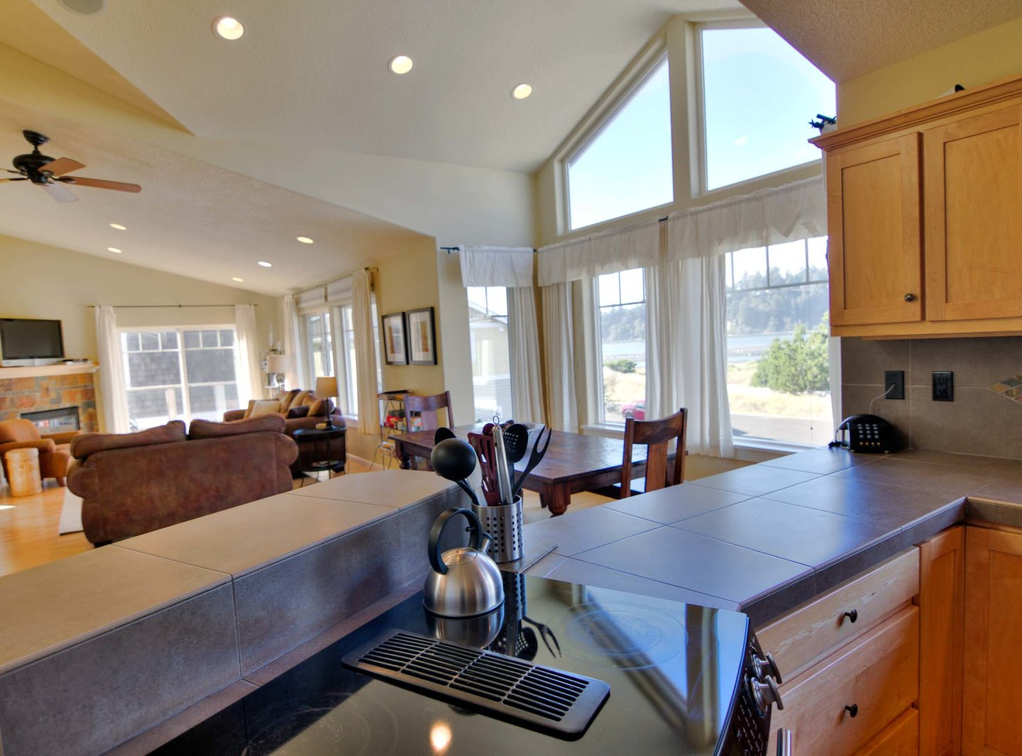 The contemporary kitchen is bathed in light, and enjoys a pleasant view as well.
