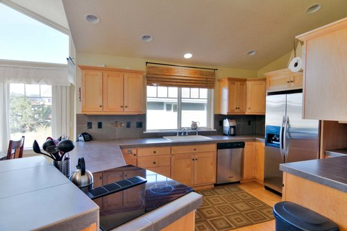The open and well equipped kitchen, with new appliances, spacious in cabinets and counters.