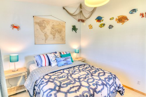 This cute second bedroom has fun coastal decor.