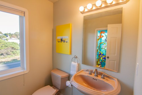 A half bath upstairs features a beautiful stained glass window.