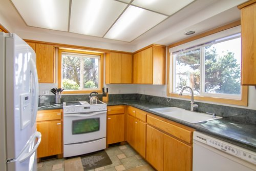 The bright kitchen has ocean views and is surrounded by trees.
