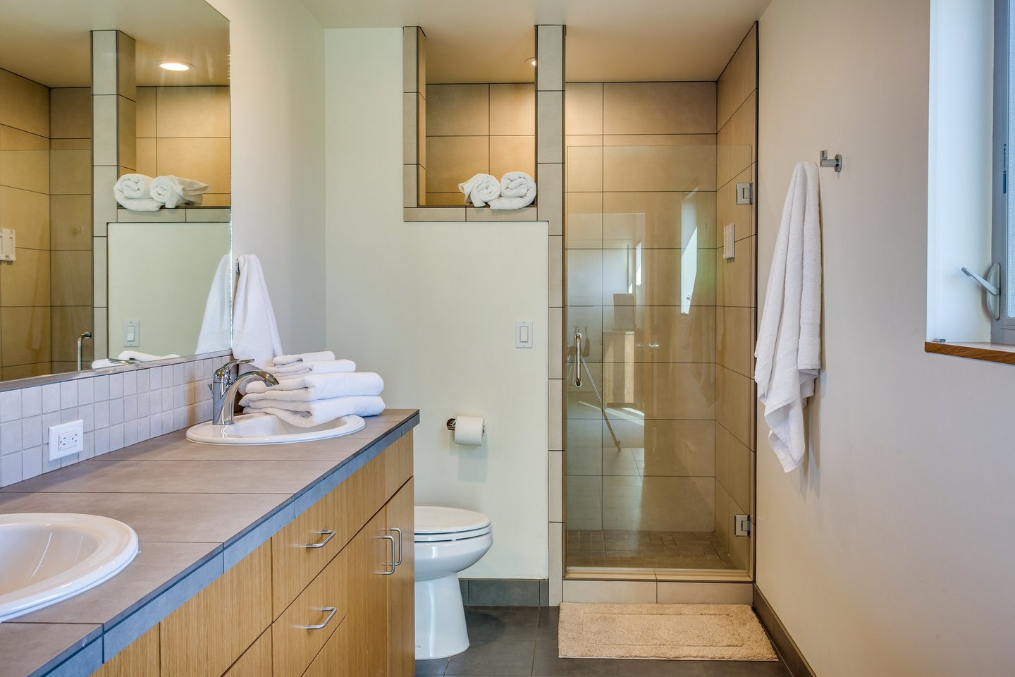 Attached to the downstairs queen bedroom is a beautiful bathroom with a tiled walk in shower.